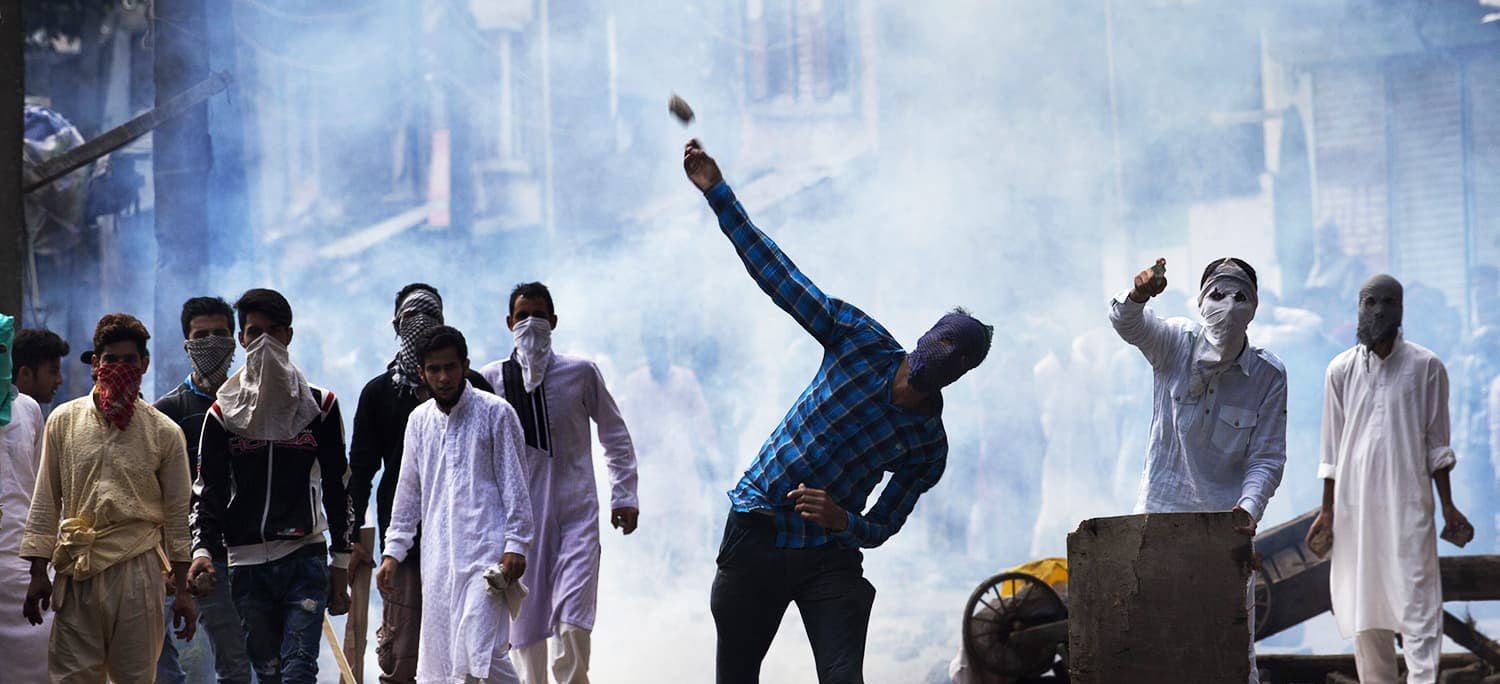 A Kashmiri throws a rock at Indian security personnel during a protest after Eidul Azha prayers in Srinagar, Sept 13, 2016. — AP/File