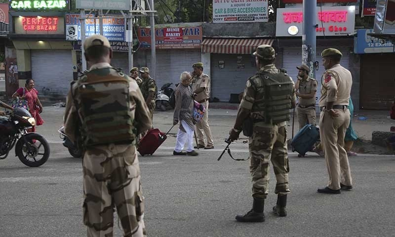 Tourists walk past Indian security forces during curfew like restrictions in IoK on Monday. — AP
