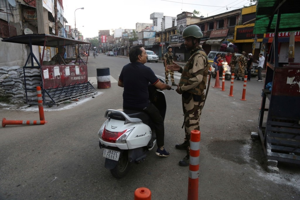 An Indian soldier stops a commuter during curfew like restrictions in IoK on Aug 5. — AP