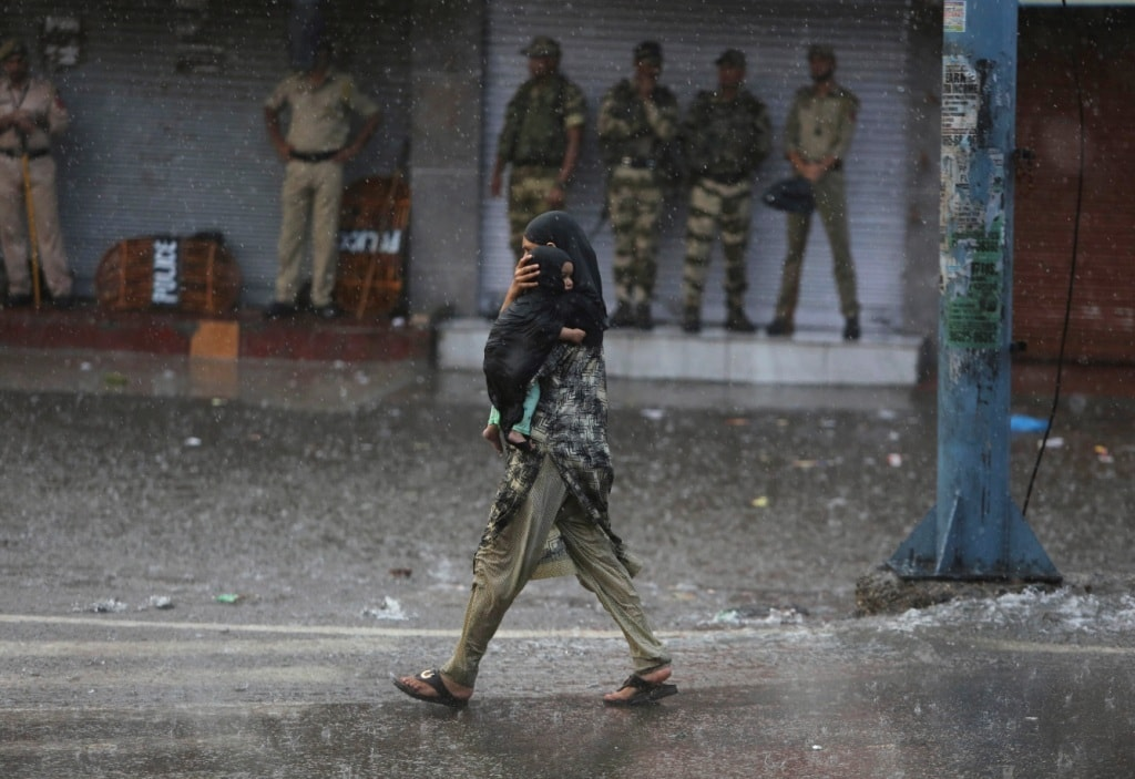 A woman carries her child as she walks past Indian security personnel as it rains during curfew like restrictions in IoK on Aug 5. — AP