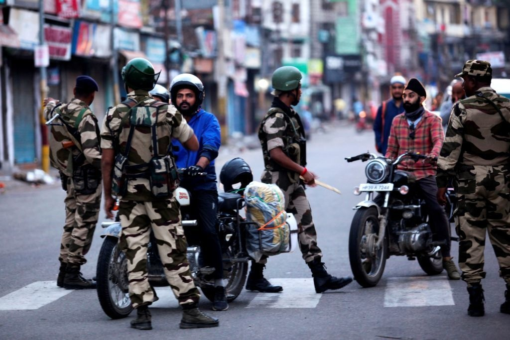 Security personnel question motorists on a street in IoK on Aug 5. — AFP
