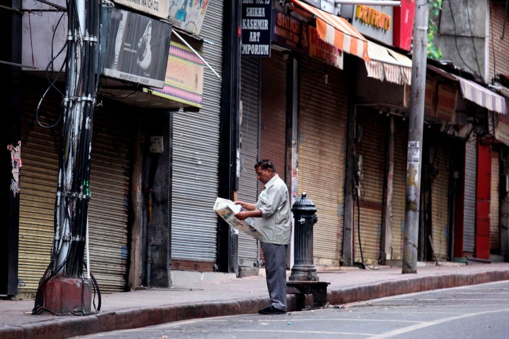 A man reads a newspaper standing in front of closed shops in Jammu on August 6, 2019. - Washington on August 4 urged respect for rights and called for the maintenance of peace along the de facto border in Kashmir after India stripped a special autonomy status from its part of the divided region. (Photo by Rakesh BAKSHI / AFP) — AFP or licensors