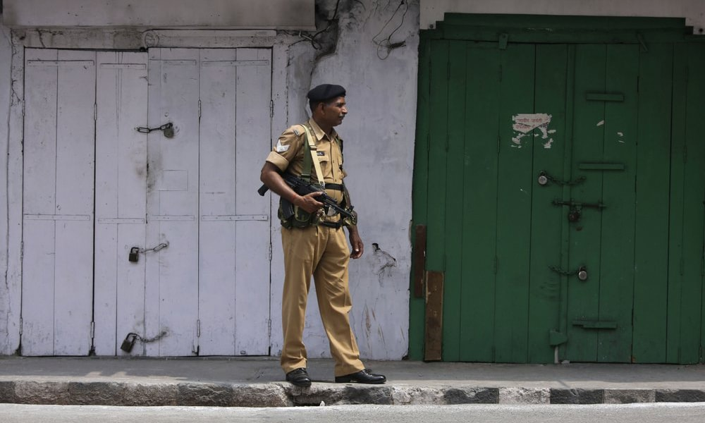 An Indian paramilitary soldier stands guard near closed shops in Jammu on Tuesday. — AP