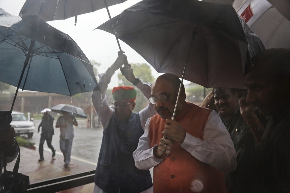 Indian Minister Amit Shah, center front, arrives at the Parliament in New Delhi on Tuesday. ─ AP