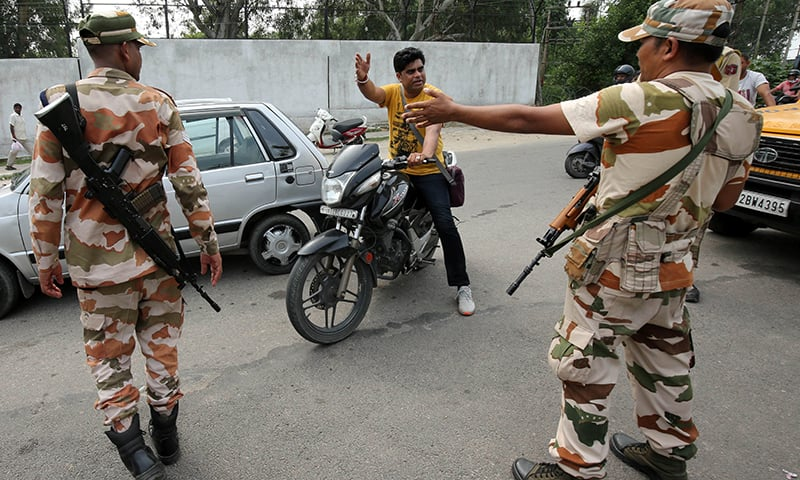 Members of Central Industrial Security Force (CISF) stop a man at a check point along a road during restrictions in Jammu on Tuesday. — Reuters