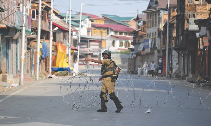 Srinagar: An Indian soldier placing barbed wire across a street during curfew on Tuesday.—AFP