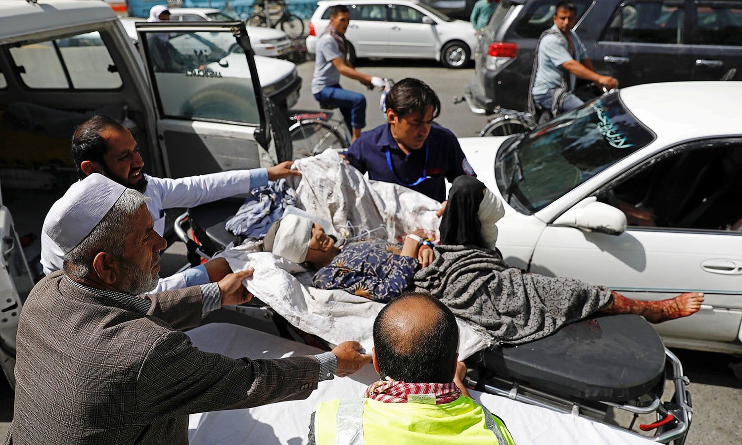 Men carry an injured woman to a hospital after a blast shook Kabul. — Reuters