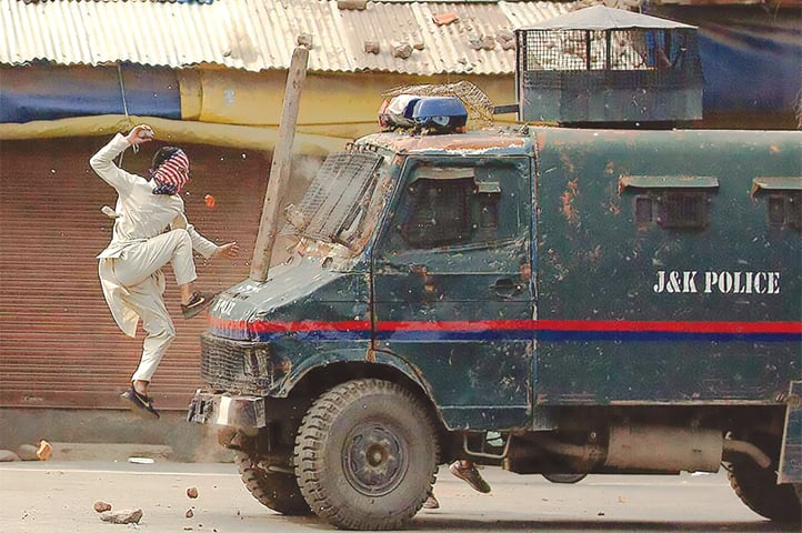 A Kashmiri protester throws stones at an armoured police vehicle during a protest in Srinagar on May 31 | Yasin Dar/AP