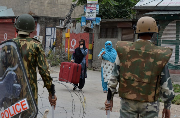 Indian paramilitary troopers stand guard as Kashmiri women approach them during a weeks' long curfew in downtown Srinagar after the death of a popular rebel leader sparked wide-scale protests | Tauseef Mustafa/AFP