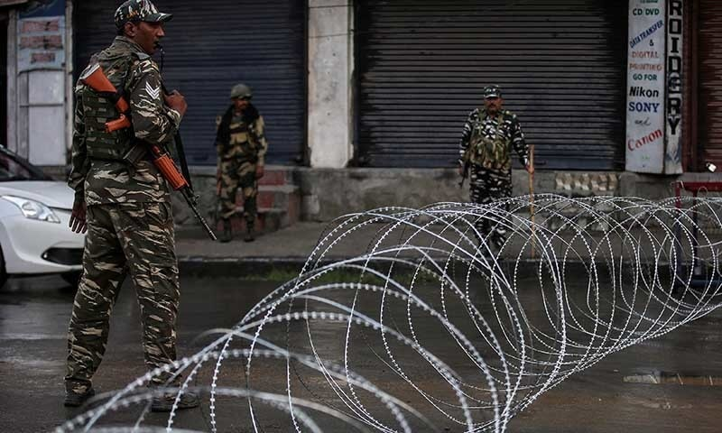 Indian security forces personnel stand guard next to concertina wire laid across a road in Srinagar on August 7. — Reuters