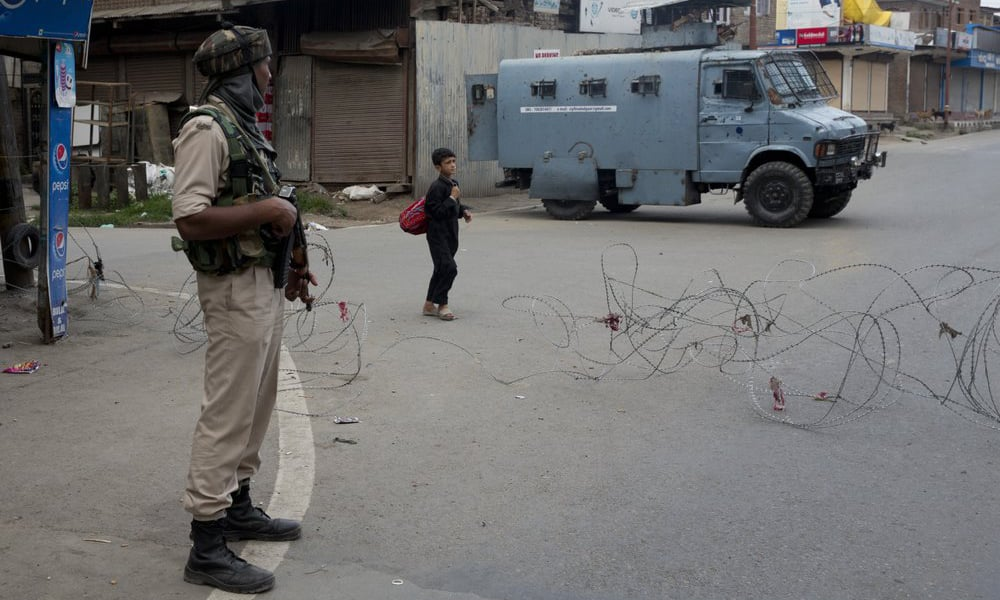 In this Aug 6, a Kashmiri boy walks past an Indian Paramilitary soldier after buying fresh bread during curfew in Srinagar. — AP