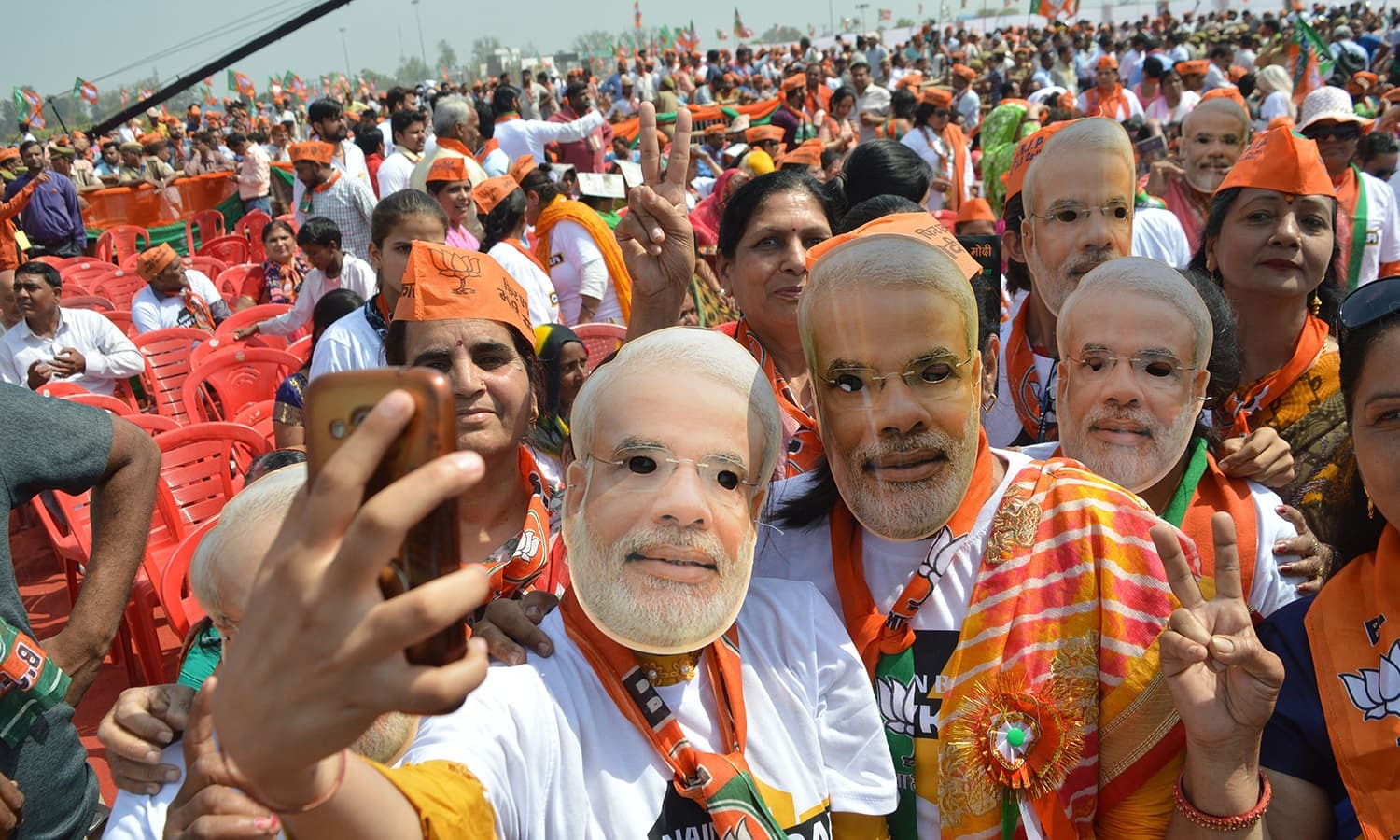 Bhartiya Janata party (BJP) take selfie pictures as they listen Prime Minister Narendra Modi speech during a rally in Meerut in Uttar Pradesh on March 28, 2019. (Photo by STR / AFP) — AFP or licensors