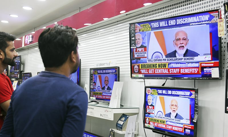 People in occupied Kashmir watch Indian Prime Minister Narendra Modi address the Indian nation in a televised speech, in an electronics store in Jammu. — AP