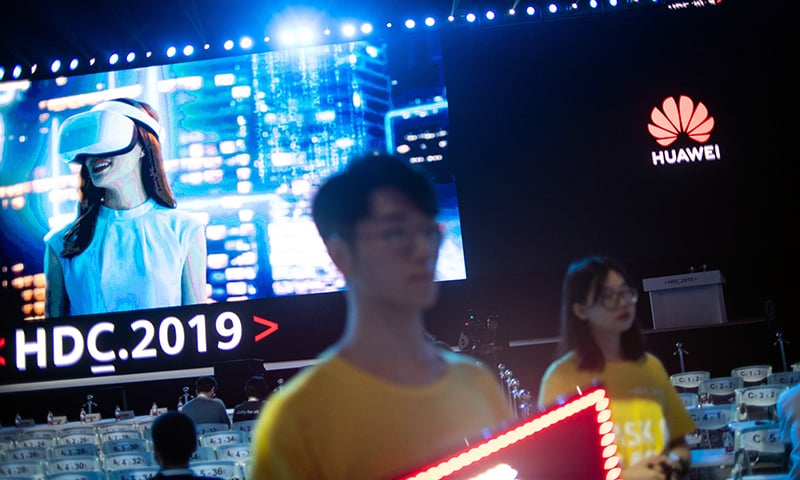 Ushers hold boards to guide guests to their seats ahead of Huawei's unveiling of its new HarmonyOS operating system in Dongguan, Guangdong province on Friday, August 9. — AFP