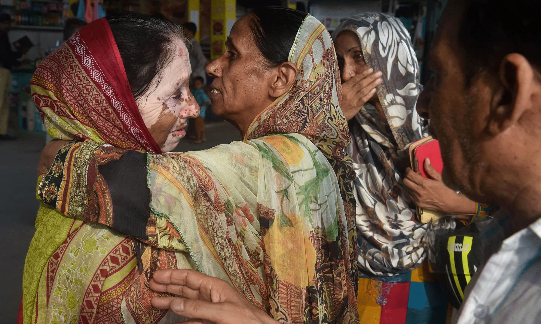 A Pakistani woman (C) embraces her Indian relative (L) ahead of her departure to India via the Samjhota Express train at the railway station in Lahore on August 8, 2019. — AFP