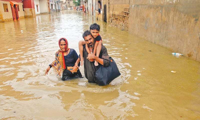 A family trudges through the water in Surjani Town, Karachi —Agencies