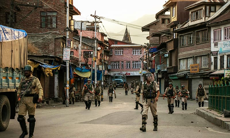 Indian security personnel walk on a street in Srinagar on August 9, 2019. — AFP