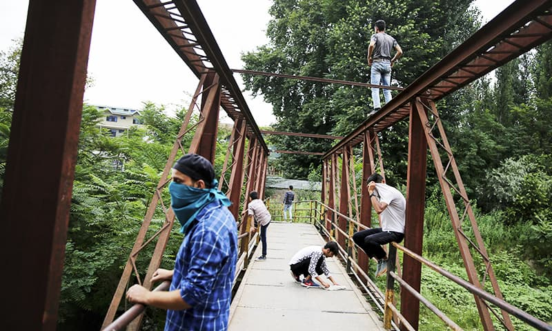 Kashmiri protesters monitor positions of Indian soldiers from a footbridge during a protest against the Indian government in Srinagar. — AP