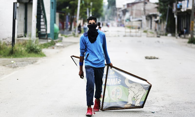 A Kashmiri protester drags an advertisement hoarding to be used as a shield during an anti-India protest in Srinagar. — AP