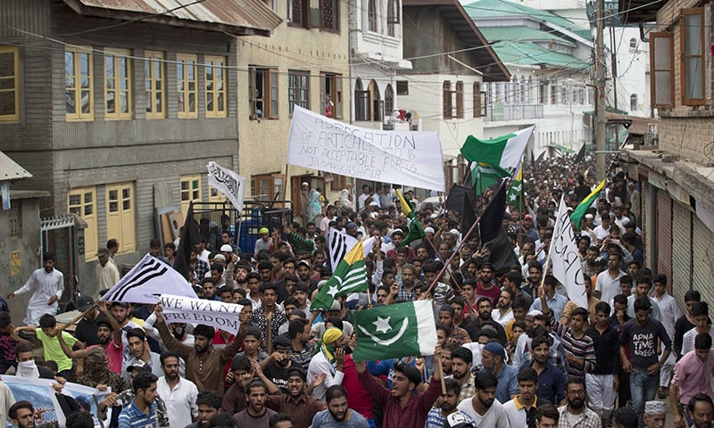 Protestors shout slogans and march on a street after Friday prayers in Srinagar, Indian-occupied Kashmir, on Friday. — AP