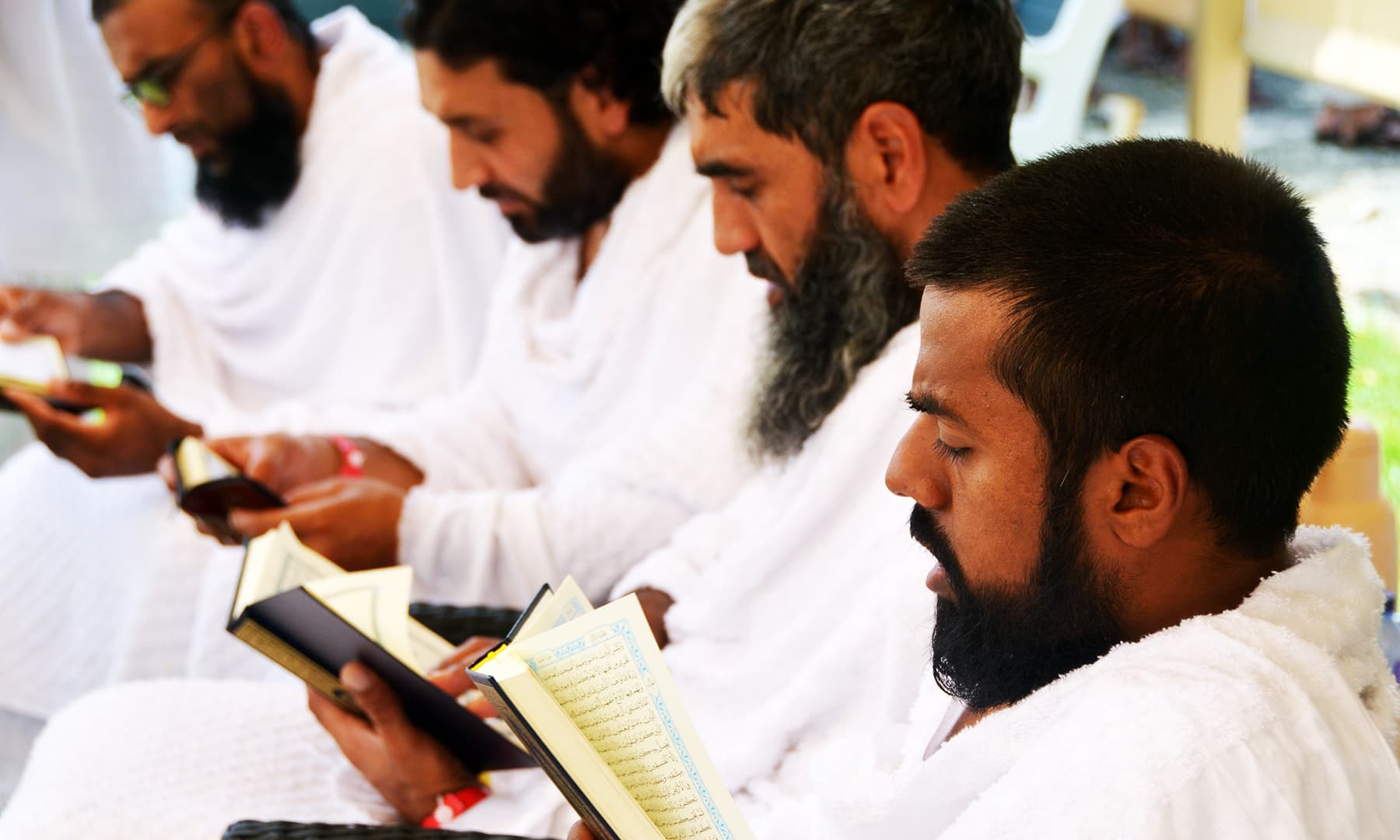 British cyclists who are pedaling all the way from London to Madina, read the Quran at their camp in Arafat, during their haj pilgrimage. — Reuters