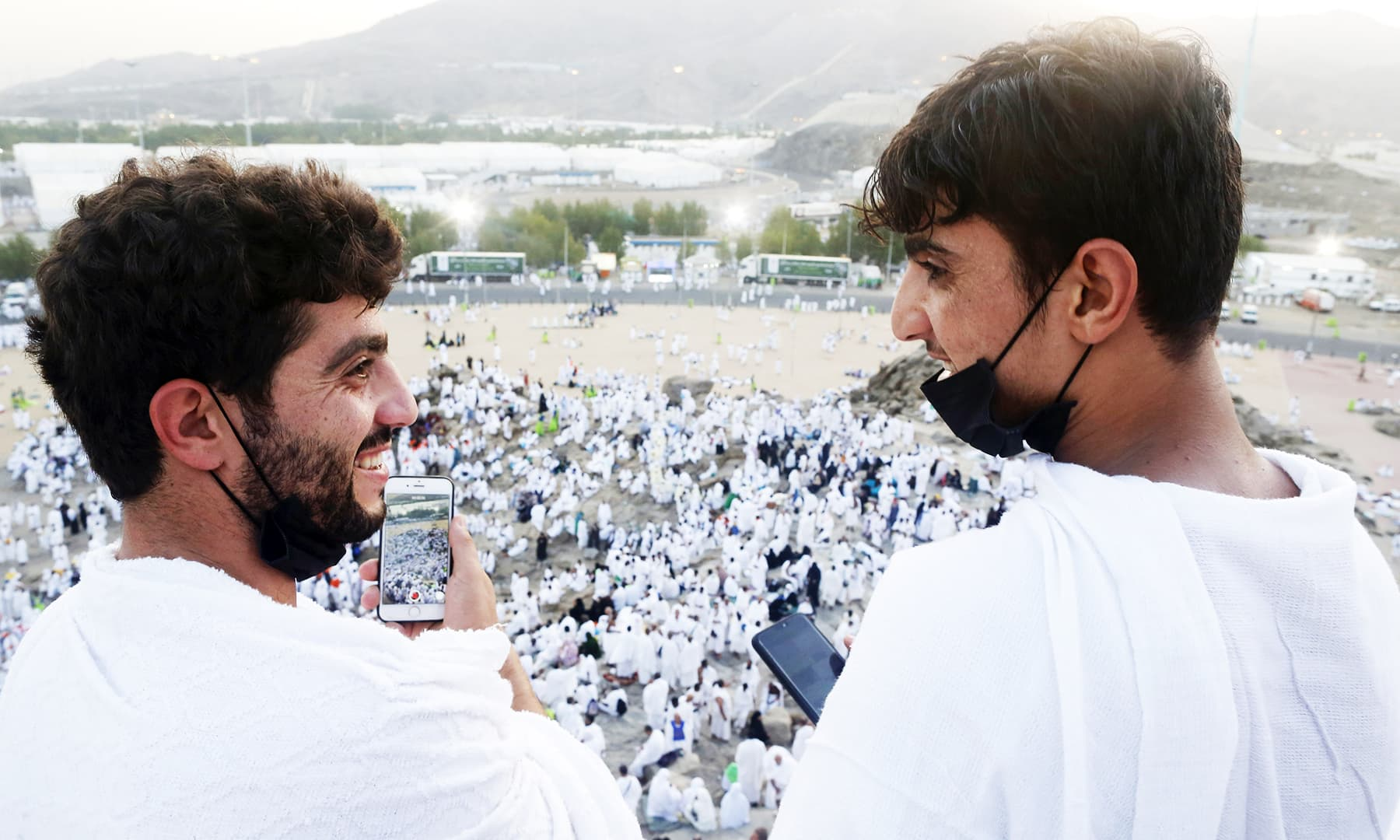 Syrian pilgrims Moiassar, left, and Abdallah, right, share a moment on a rocky hill known as Mountain of Mercy, on the Plain of Arafat during the annual hajj pilgrimage. — AP