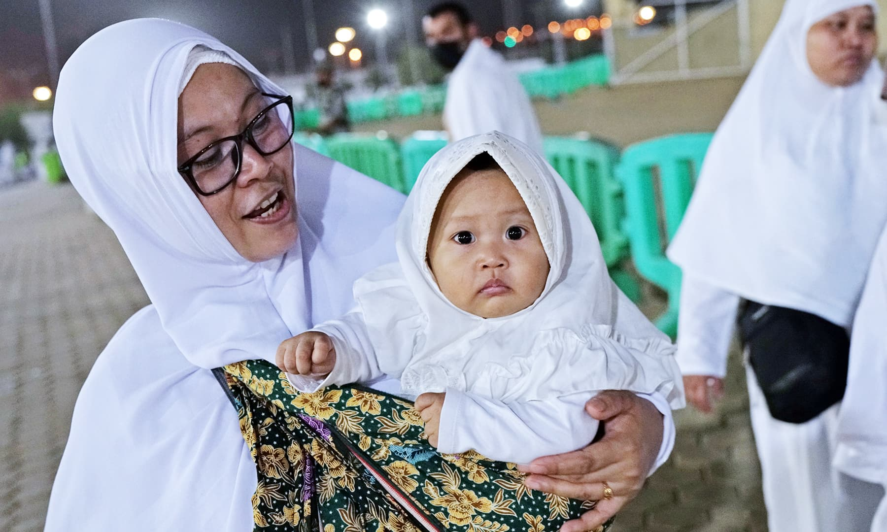 A woman carries her baby as she walks through Mount Mercy on the plains of Arafat during the annual haj pilgrimage. — Reuters