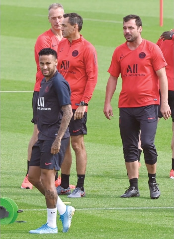PSG's Neymar stands next to assistant coaches (back L to R) Rainer Schrey, Arno Michels and Zsolt Loew as he attends a training session of the club in Saint-Germain-en-Laye on Saturday.—AFP
