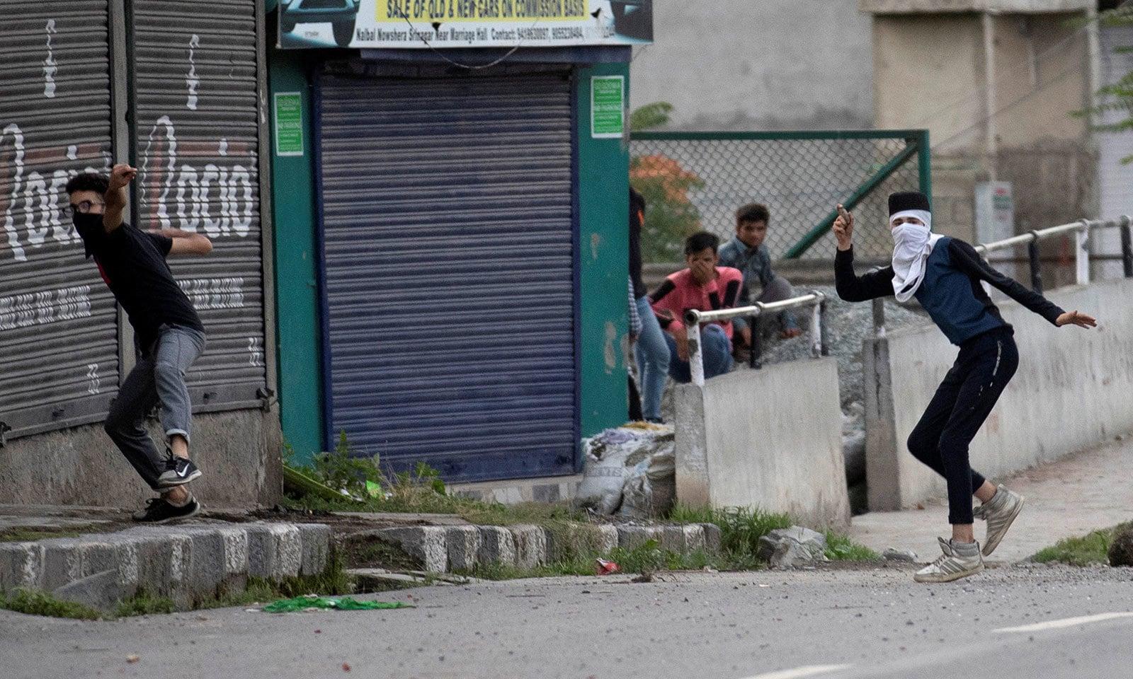 کشمیری نوجوان پولیس کی شیلنگ کا جواب پتھر سے دیتے رہے—فوٹو:رائٹرز