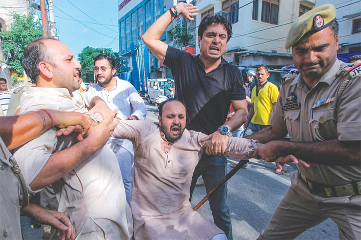 JAMMU: Police taking an activist of Jammu and Kashmir Youth Congress into custody during a protest against the Indian government on Saturday.—AFP