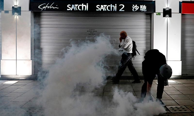 A man walks past an anti-extradition bill protester as he tries to pick up a tear gas canister at Tsim Sha Tsui after a demonstration in Hong Kong, China on August 10. — Reuters