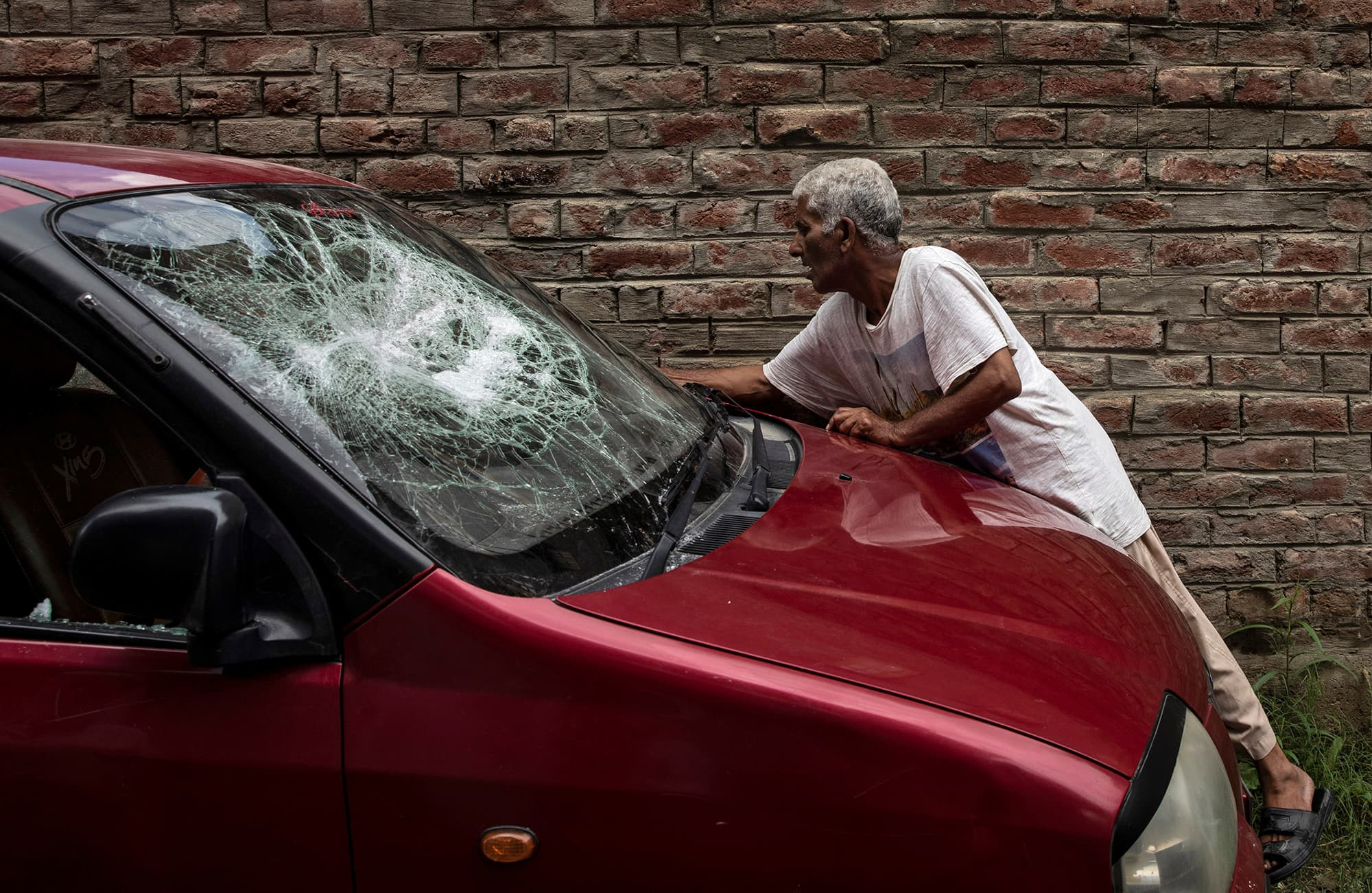 A Kashmiri man inspects his car which was allegedly damaged by Indian security forces after clashes between protesters and the security forces during curfew in Srinagar. ─ Reuters