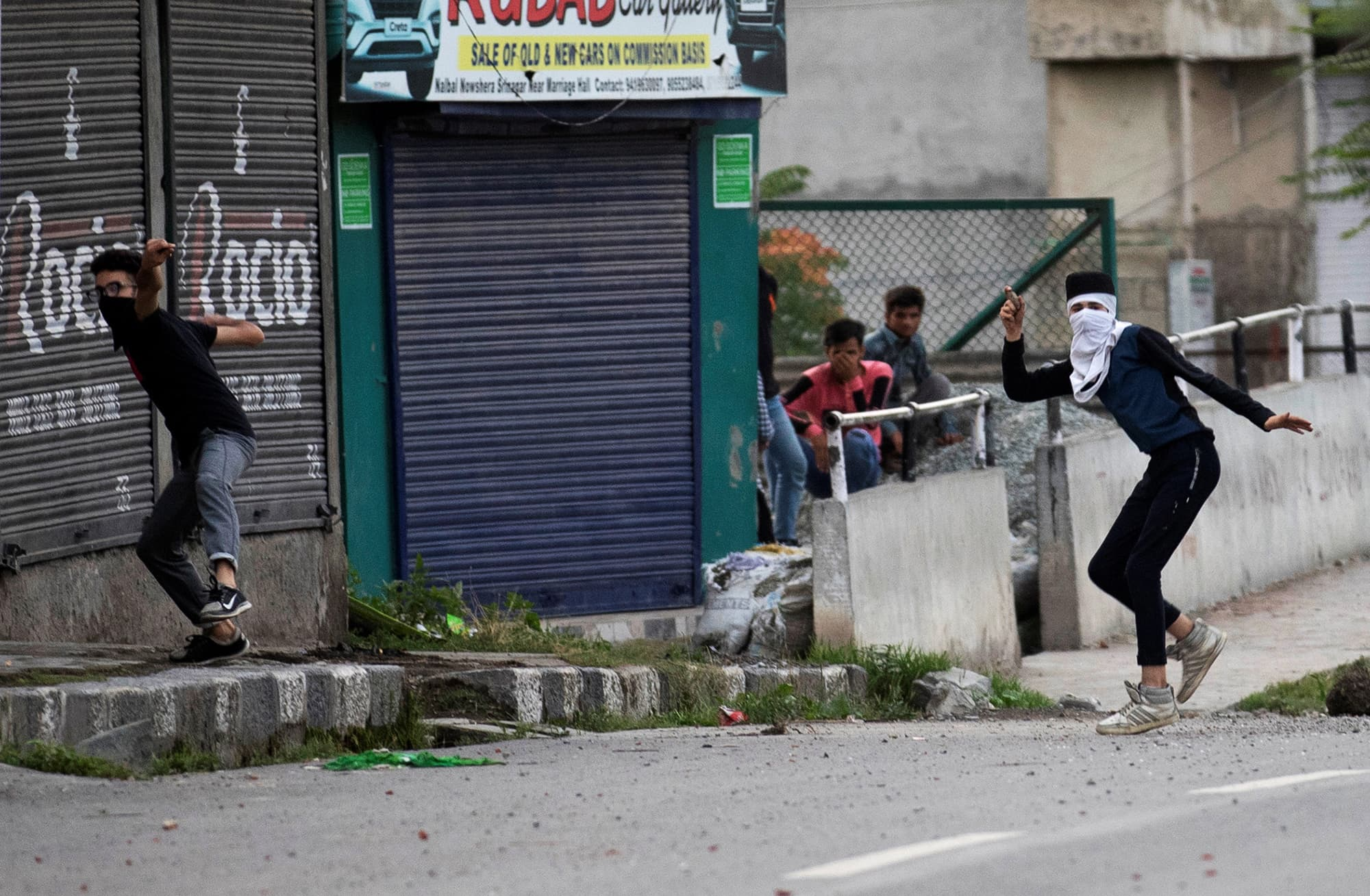 Kashmiri youth throw stones, a common mode of resistance in the occupied territory, at Indian security forces during curfew in Srinagar. ─ Reuters