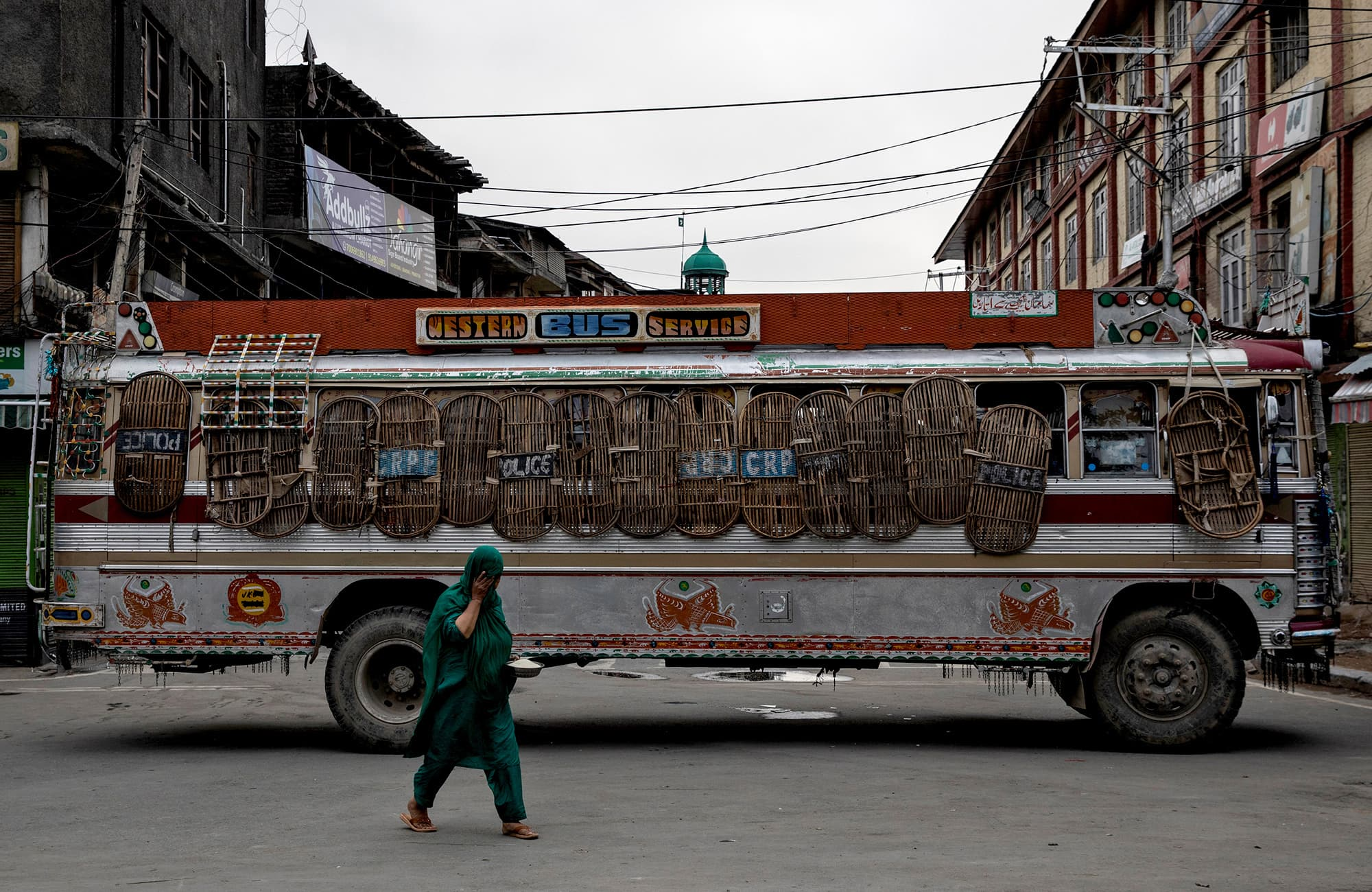 A Kashmiri woman walks past a bus used as a roadblock by Indian security personnel during curfew in Srinagar. ─ Reuters