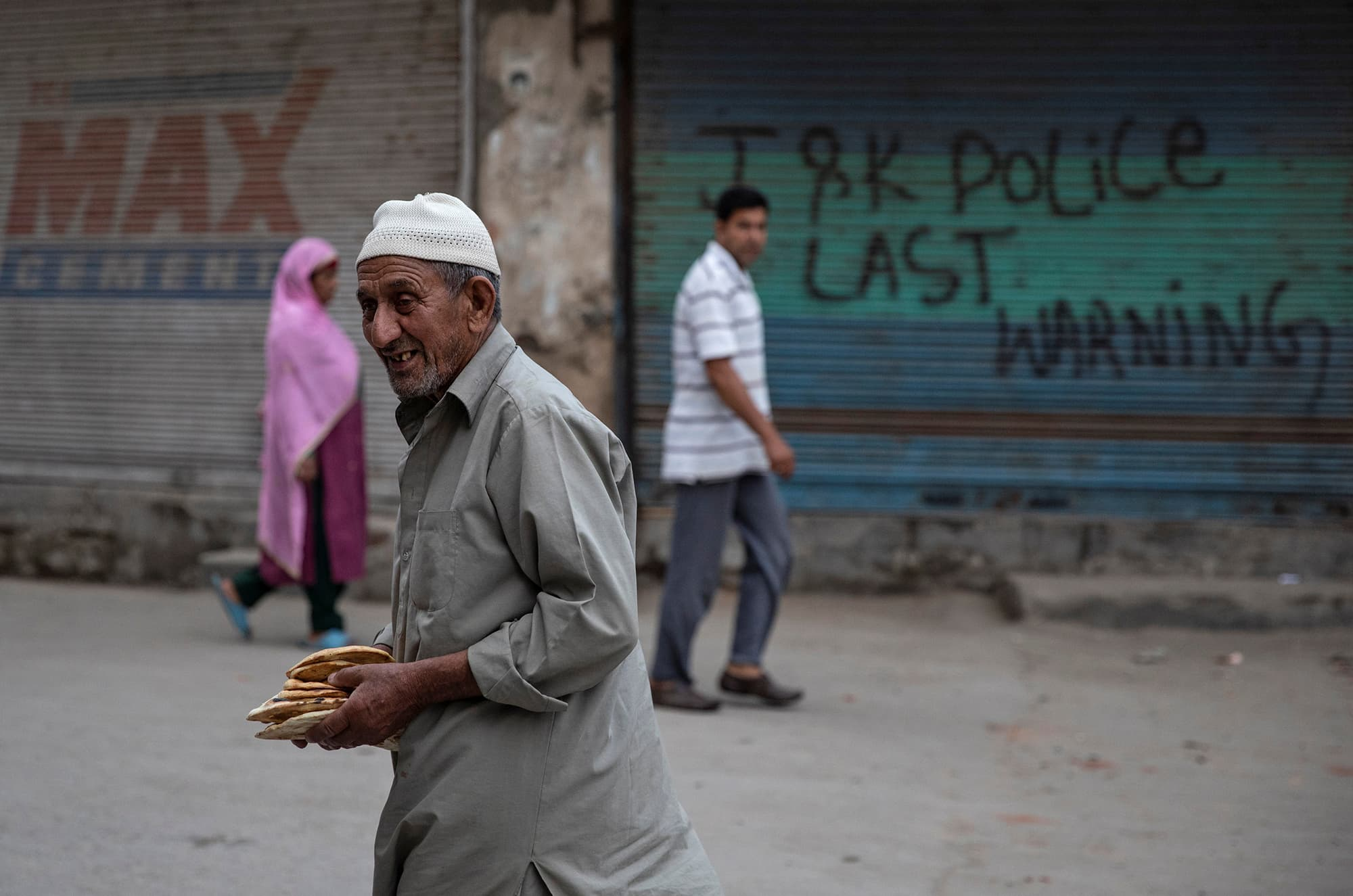 Residents of Srinagar walk along a street under curfew. ─ Reuters