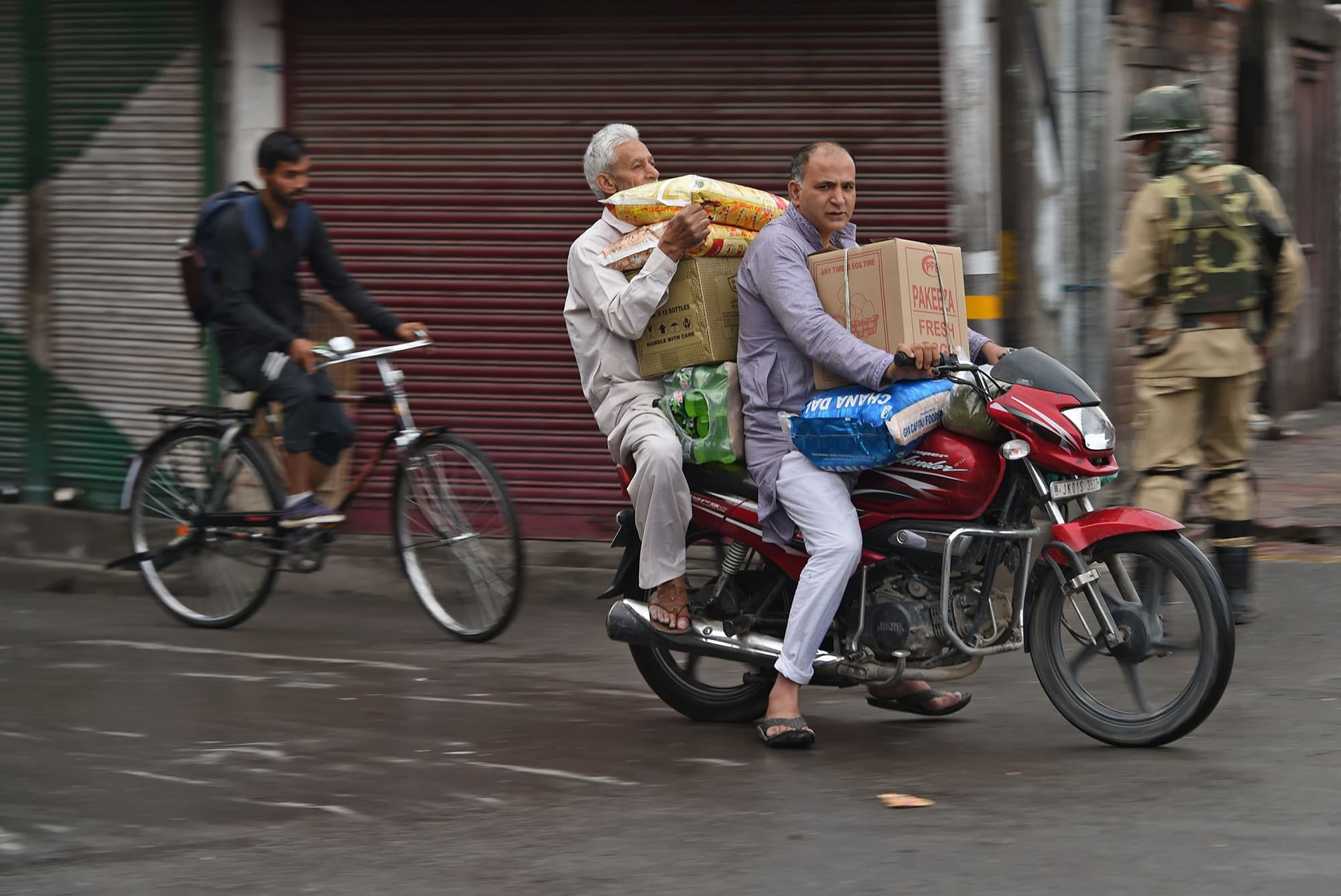 Two men ride a motorcycle as they carry packages of food during a lockdown and curfew in Srinagar. ─ AFP