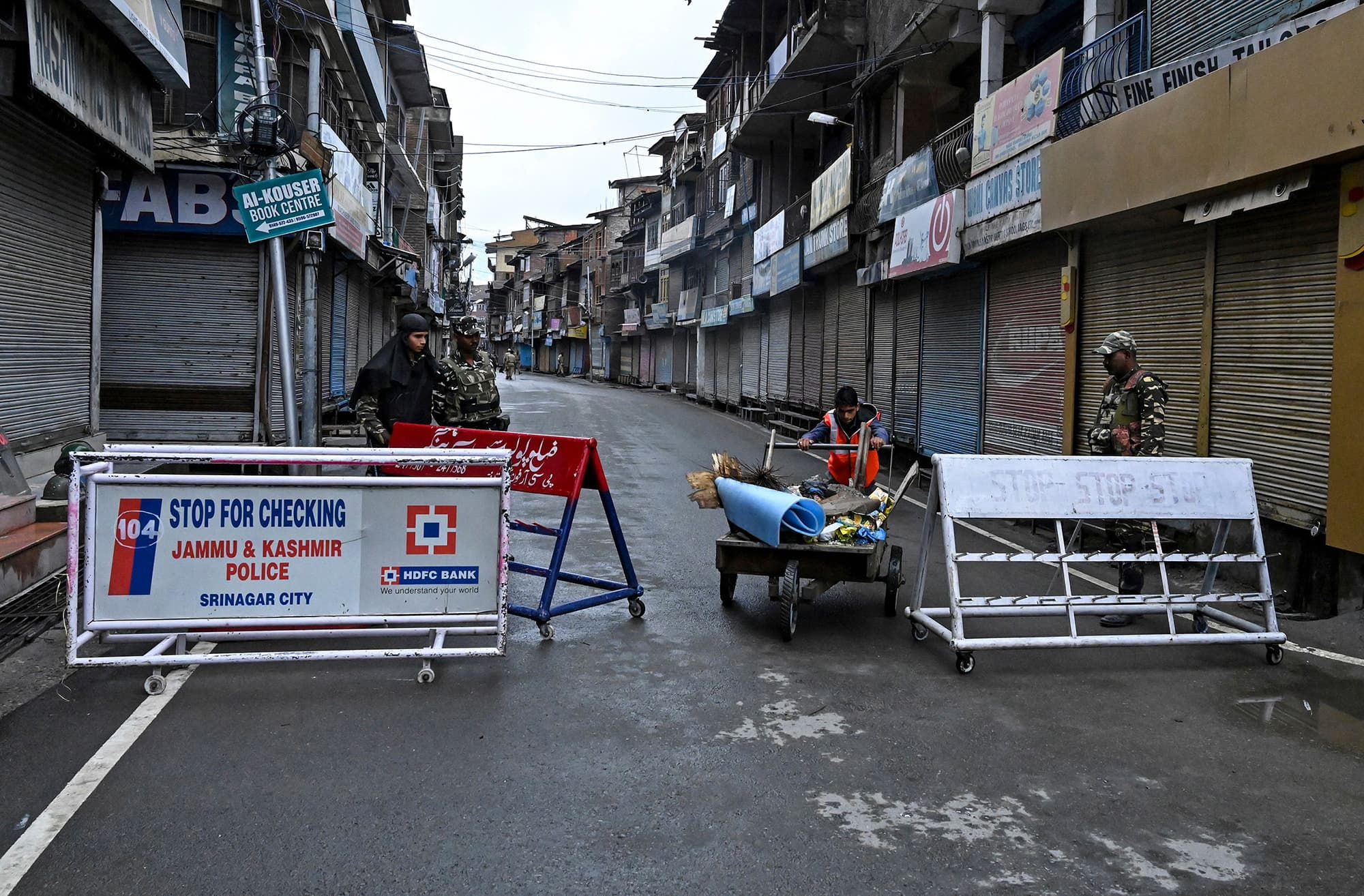 Security personnel stand guard as a municipal worker pushes a handcart during curfew in Srinagar. ─ AFP