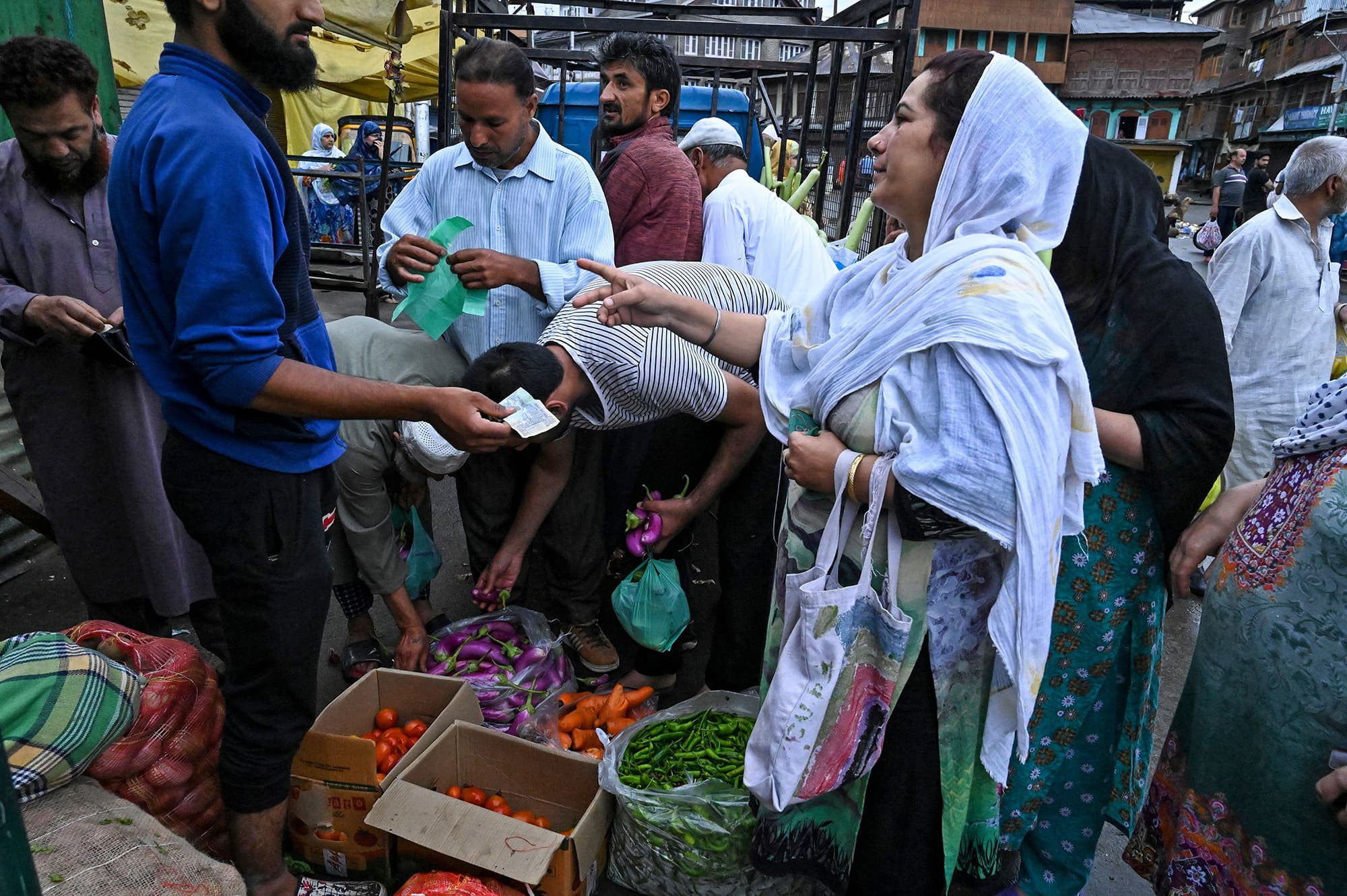 Kashmiris purchase food and vegetables during a lockdown in Srinagar. ─ AFP