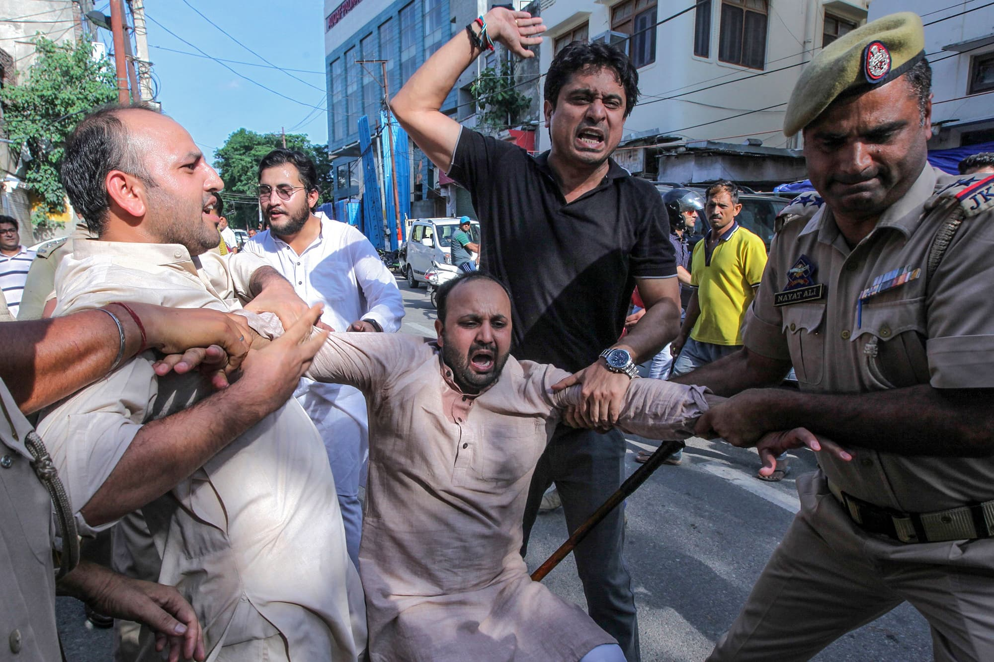 Police personnel struggle to detain an activist of the Jammu and Kashmir Youth Congress during a protest against the Indian government in Jammu. ─ AFP