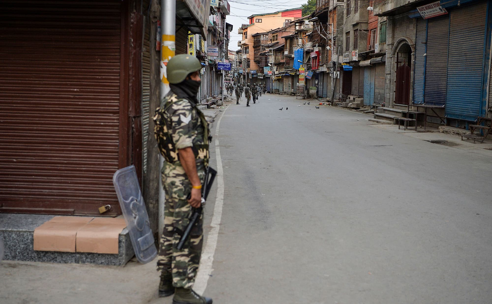 Security personnel patrol along a street in Srinagar. ─ AFP