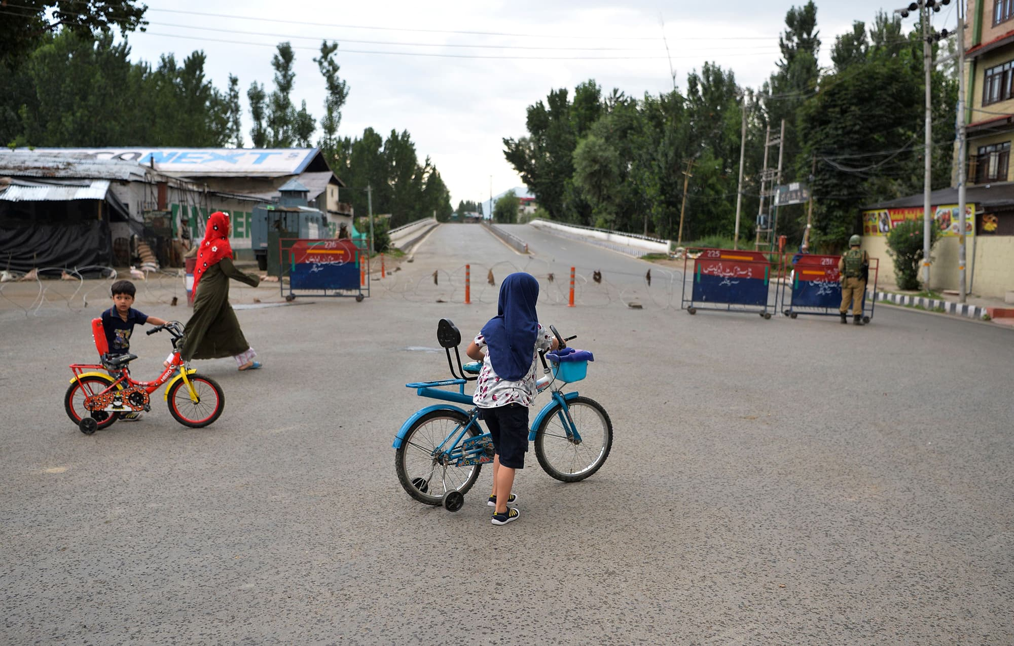 A woman and two children with their bikes cross a deserted street in Srinagar as the widespread restrictions on movement and a telecommunications blackout remain in place. ─ AFP