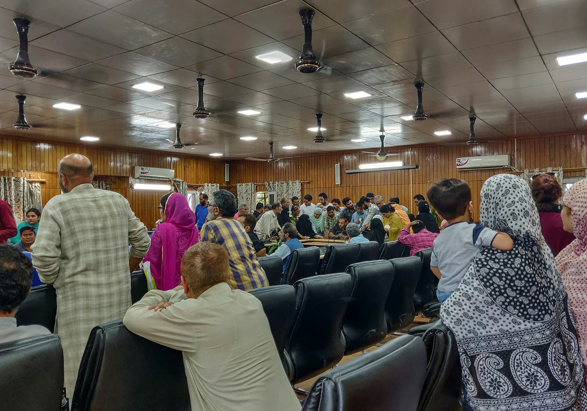 Kashmiris crowd around an official to use a phone at a government office in Srinagar as all communications remain suspended by the Indian government amid lockdown. ─ Reuters