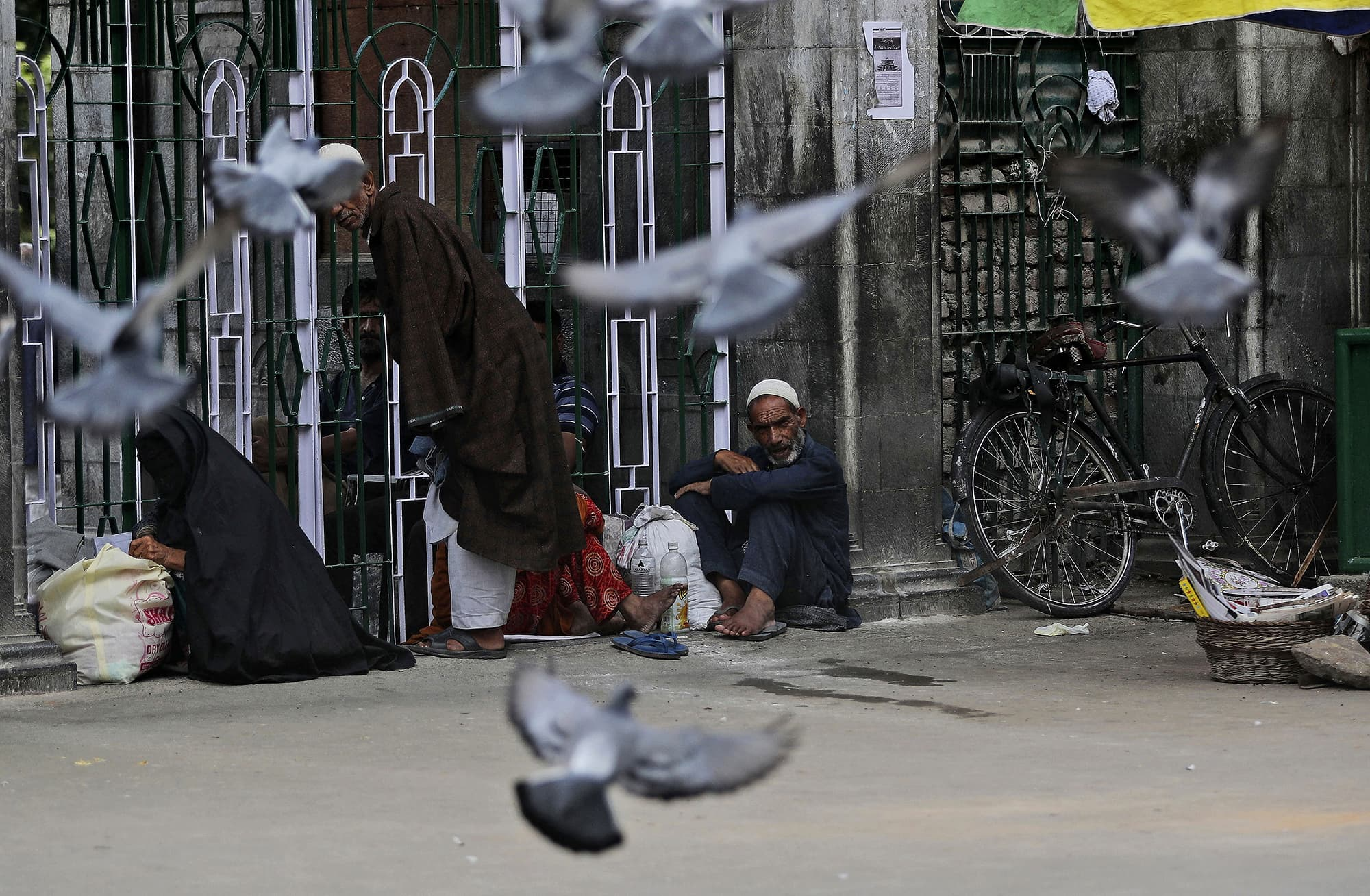 People sit outside a Muslim shrine on Friday as Srinagar remains under curfew. ─ AP