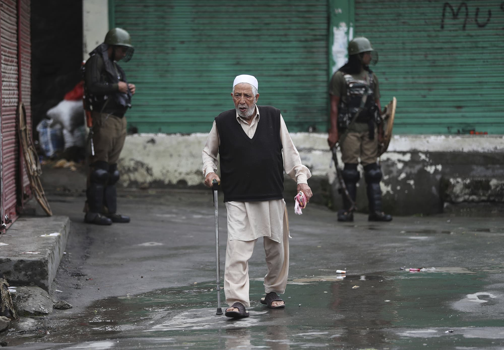 An elderly Kashmiri man crosses a road as Indian paramilitary soldiers stand guard in Srinagar ─ AP