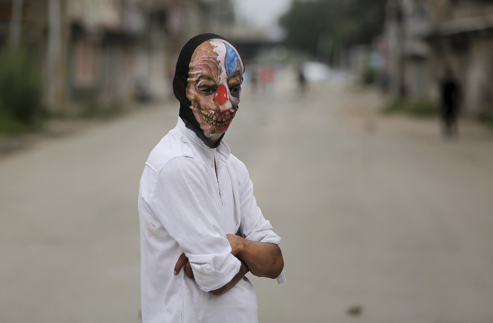 A Kashmiri youth wears a mask to hide his identity as he participates in an anti-India protest as Srinagar remains under curfew. ─ AP