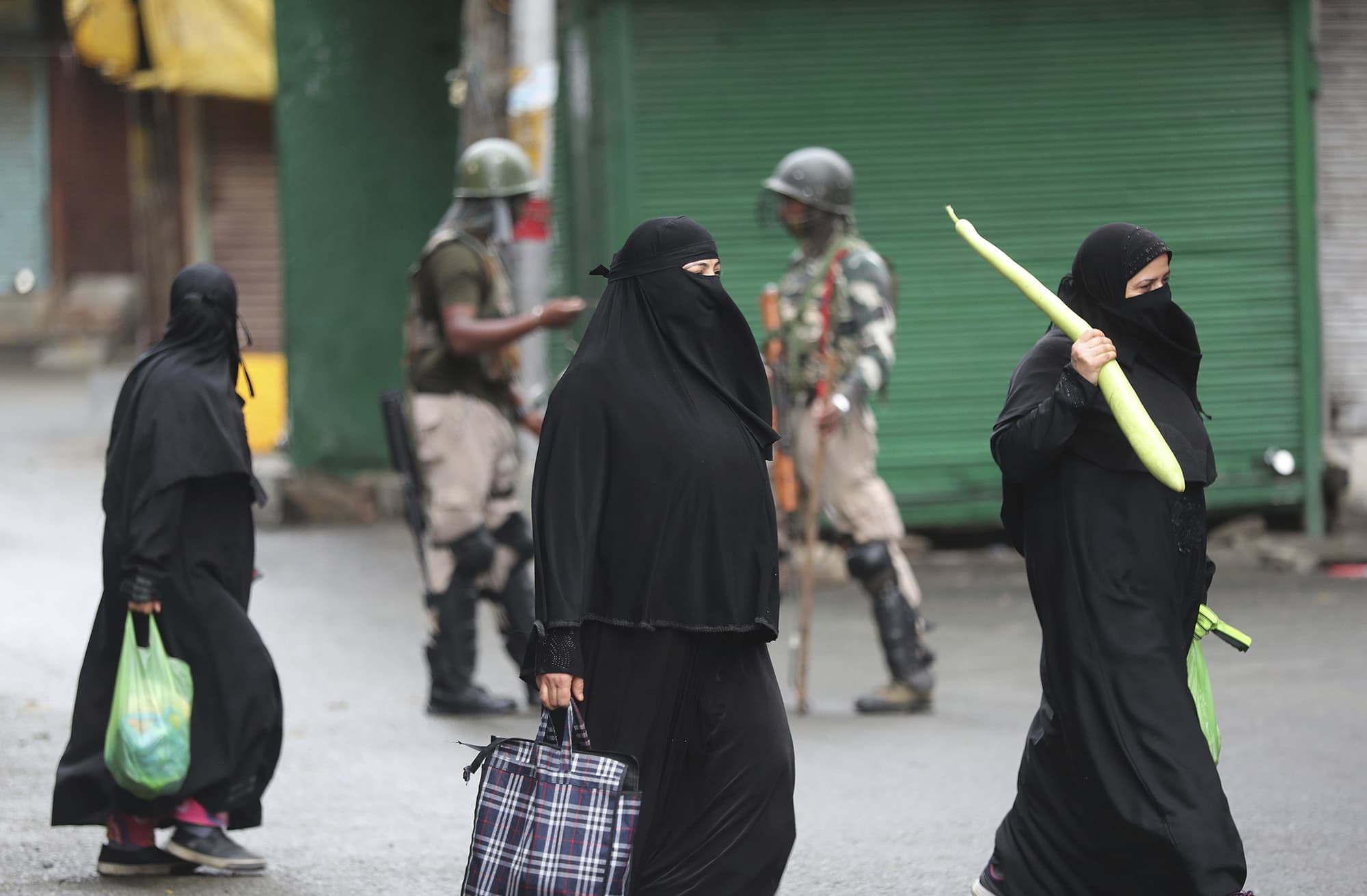 Kashmiri women hold bags filled with essentials and walk past Indian paramilitary soldiers closing off a street in Srinagar. ─ AP