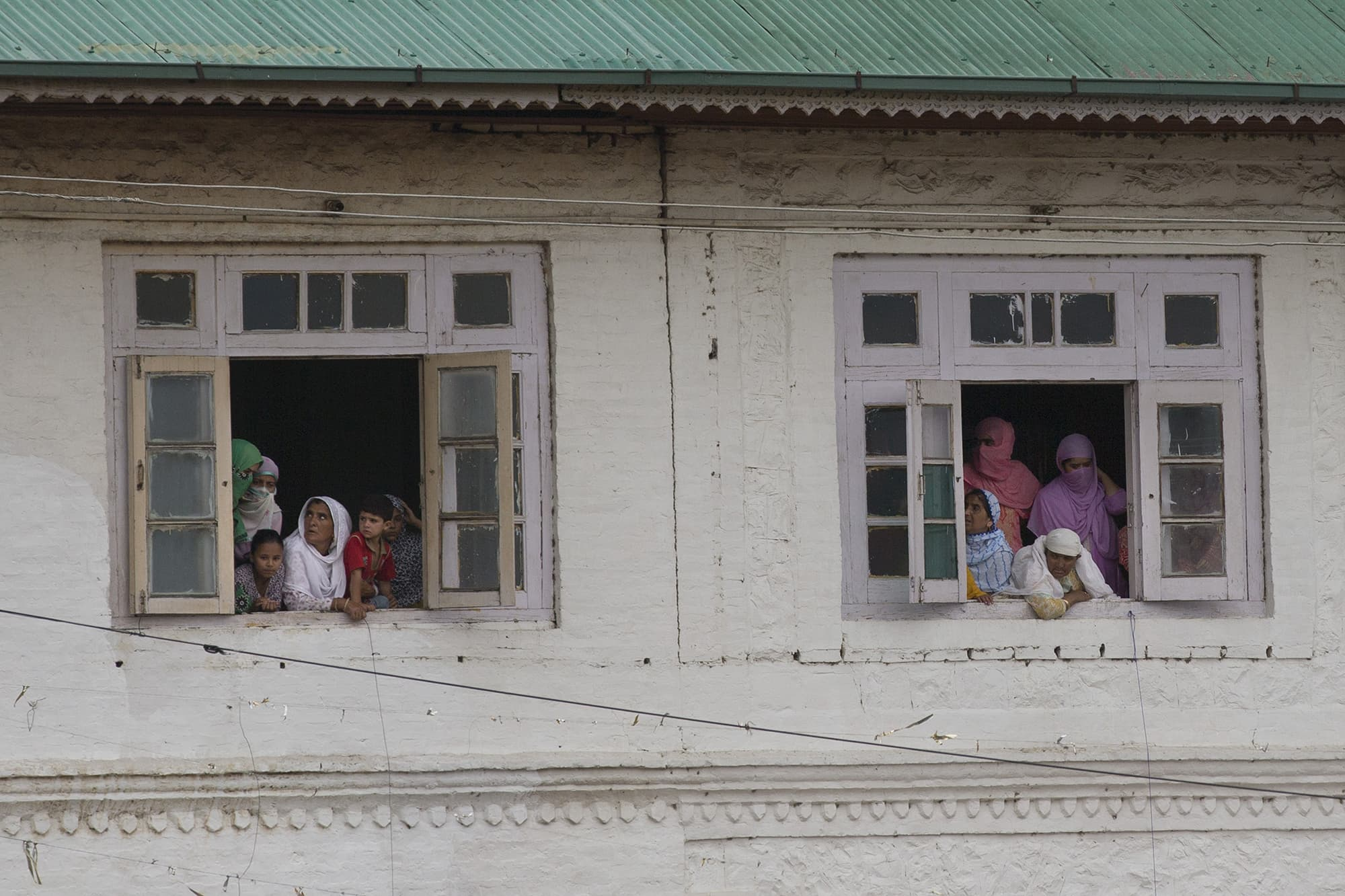 Kashmiri women watch a protest march from the window of a mosque in Srinagar. ─ AP
