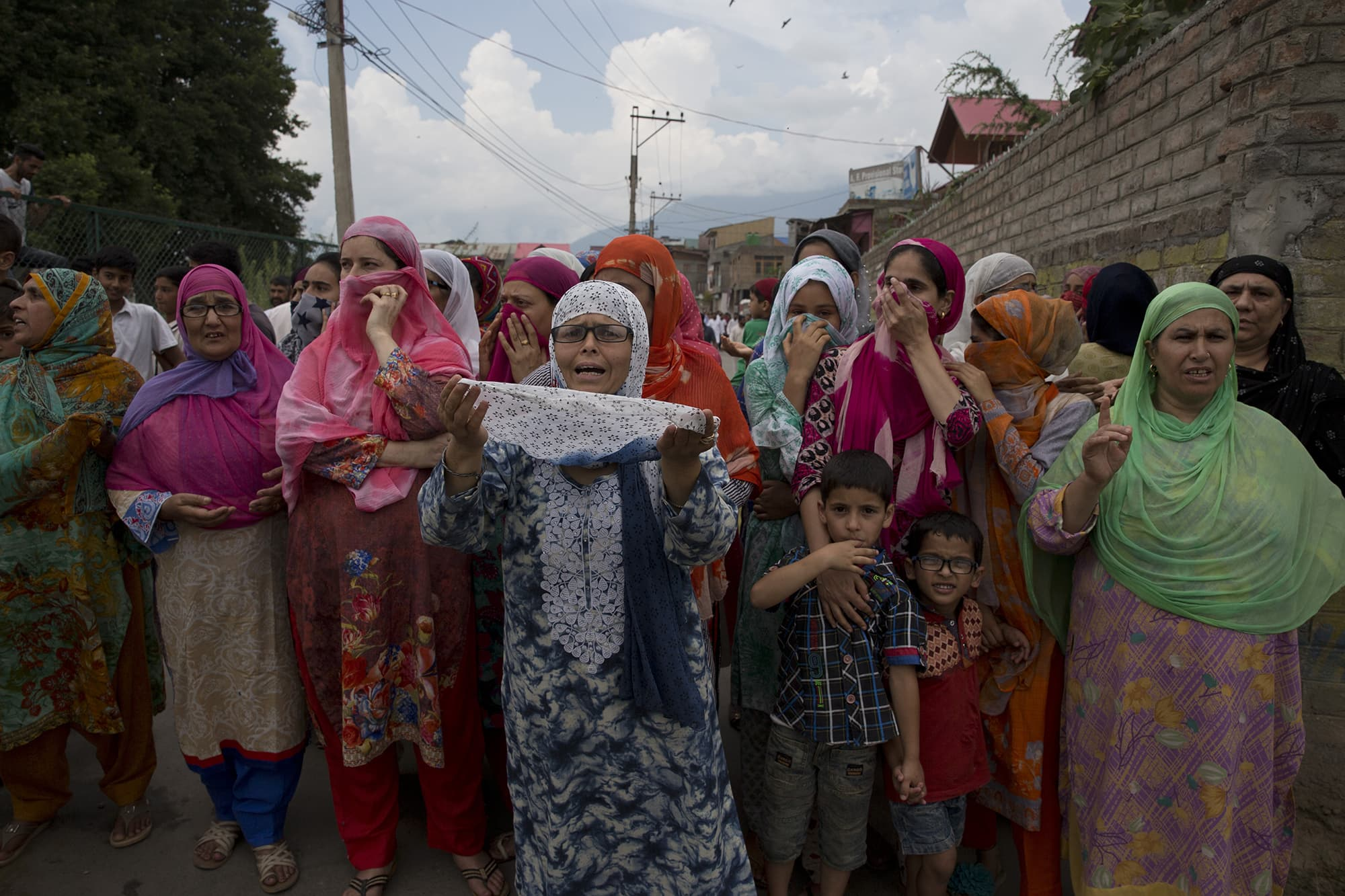 A Kashmiri woman prays as she watches a protest march in Srinagar. ─ AP