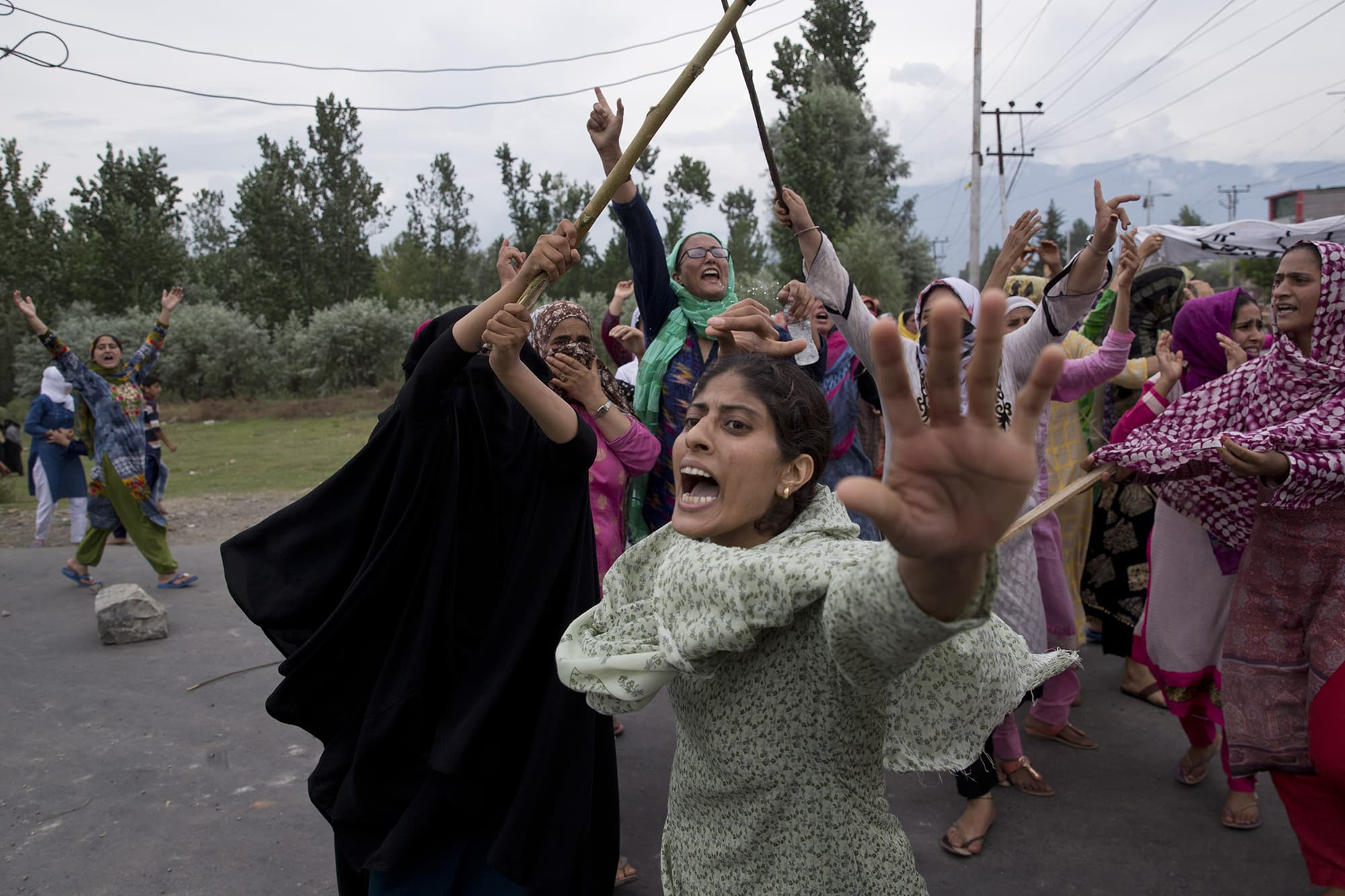Kashmiri women shout slogans as Indian policemen fire teargas and live ammunition in the air to stop a protest march against the Indian government in Srinagar under curfew. ─ AP