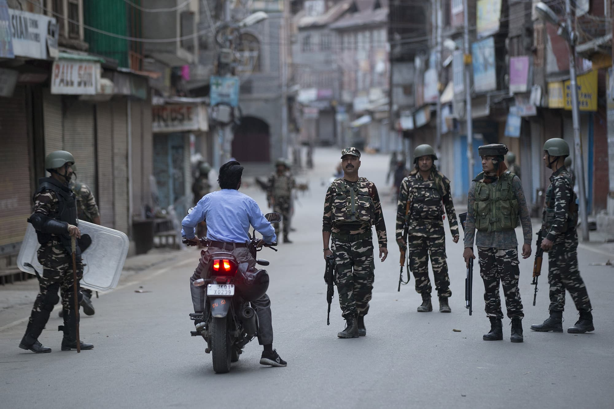 Indian paramilitary soldiers question a citizen on a motorcycle during curfew in Srinagar. ─ AP